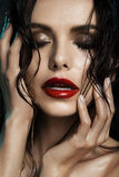 Girl with wet skin. Closeup portrait of beautiful young woman with wet skin and glossy red lips over dark background Stock Photography