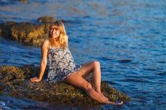 Girl in a wet sundress on the rocks stock photos