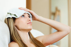 Girl with wet towel on forehead Stock Images