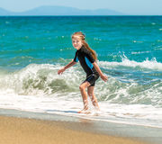 Girl in a wetsuit on the beach Royalty Free Stock Images