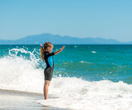 Girl in a wetsuit on the beach. Happy little girl playing in a wetsuit on the beach Stock Image