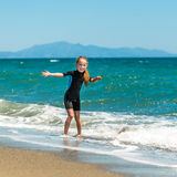 Girl in a wetsuit on the beach. Laughing  little girl playing in a wetsuit on the seashore Royalty Free Stock Photo