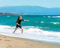 Girl in a wetsuit on the beach Stock Image