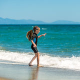 Girl in a wetsuit on the beach Royalty Free Stock Photography