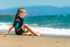 Girl in a wetsuit on the beach. Little girl sitting in a wetsuit on the beach Royalty Free Stock Images