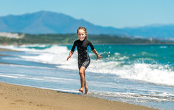 Girl in a wetsuit running along the beach Stock Photos