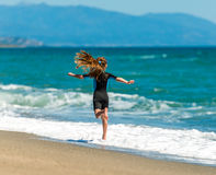 Girl in a wetsuit running along the beach Stock Images