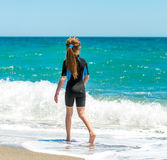 Girl in a wetsuit running along the beach. Little girl in a wetsuit walking on the seashore. back view Royalty Free Stock Image