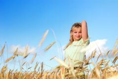 Girl in wheat field. Pretty young girl standing in golden wheat field Stock Image