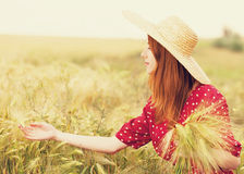 Girl at wheat field. Redhead girl in red dress at wheat field Stock Photography