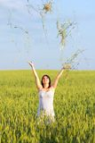 Girl in a wheat field throws ears Stock Image