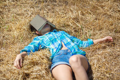 Girl in wheat holding book Stock Photography