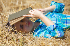 Girl in wheat holding book Stock Photos