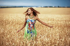 Girl in wheat meadow. Photo of glad girl enjoying life in wheat meadow Royalty Free Stock Photo