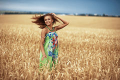 Girl in wheat meadow. Photo of glad girl enjoying life in wheat meadow Stock Images