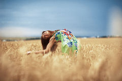 Girl in wheat meadow. Photo of glad girl enjoying life in wheat meadow Royalty Free Stock Photography