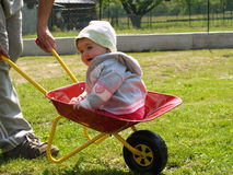 Girl in wheelbarrow Stock Images