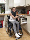 Girl on wheelchair. Disabled girl working in kitchen Royalty Free Stock Photo
