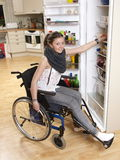Girl on wheelchair. Disabled girl working in kitchen Royalty Free Stock Image