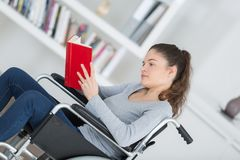 Girl in wheelchair with book Royalty Free Stock Images