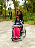 Girl on the wheelchair with friend Stock Photos