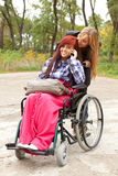 Girl on the wheelchair with friend Royalty Free Stock Photography