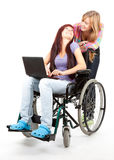 Girl on the wheelchair with friend and aptop Royalty Free Stock Photo