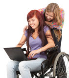 Girl on the wheelchair with friend and laptop. Invalid girl on the wheelchair with laptop and her friend Stock Photography