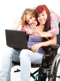 Girl on the wheelchair with friend and laptop Stock Image