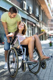 Girl in wheelchair with friend outdoor Royalty Free Stock Image