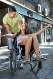 Girl in wheelchair with friend outdoor Royalty Free Stock Photography