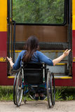 Girl on wheelchair having problem with entering the tramway Stock Images