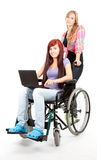 Girl on the wheelchair with laptop and her friend Stock Photos