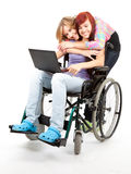 Girl on the wheelchair with laptop and her friend Royalty Free Stock Photography