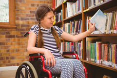 Girl in wheelchair selecting book in library Royalty Free Stock Photography