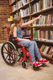 Girl in wheelchair selecting book in library Stock Photos