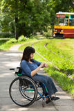 Girl on wheelchair waiting for tram Royalty Free Stock Photos
