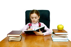 Girl which reads a book at the writing table Stock Photos