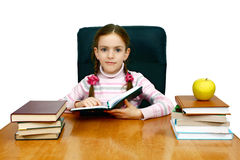 Girl which reads a book at the writing table Royalty Free Stock Image