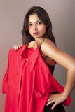 Girl which tries on red shirt in shop Royalty Free Stock Photography
