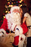 Girl whisper something to Santa Claus Royalty Free Stock Images