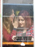Girl whispering into another girls ear Royalty Free Stock Images