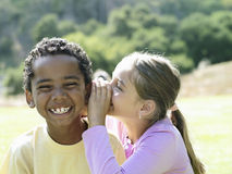 Girl (7-9) whispering in boy's (7-9) ear, boy smiling, close-up royalty free stock photos