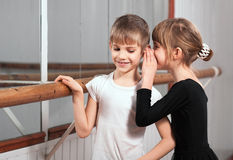 Girl a word in one's boy's ear near barre Royalty Free Stock Images