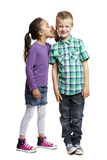 Girl whispering in boys ear Stock Photo