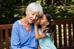 Girl whispering in ears of grandmother while sitting on wooden bench Royalty Free Stock Photo