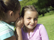 Girl (7-9) whispering in friend's ear, smiling, close-up Stock Photography