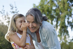 Girl Whispering In Grandmother's Ear. Closeup of a young girl whispering in grandmother's ear outdoors stock photo