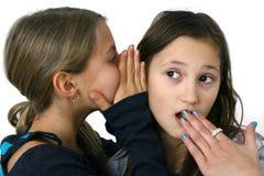 Girl whispering a secret stock images