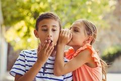 Girl whispering a secret in boys ear. In school Stock Image